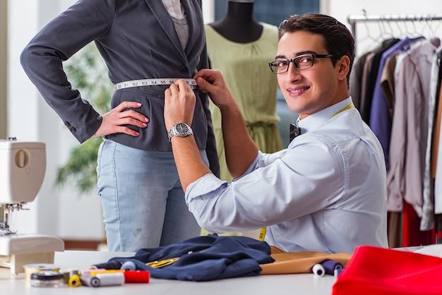 Jeune homme tailleur travaillant avec une cliente Photo Premium
