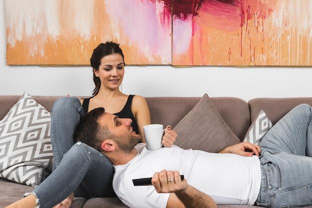 Jeune homme, tasse à café, et, télécommande, mensonge, sur, femme Photo gratuit