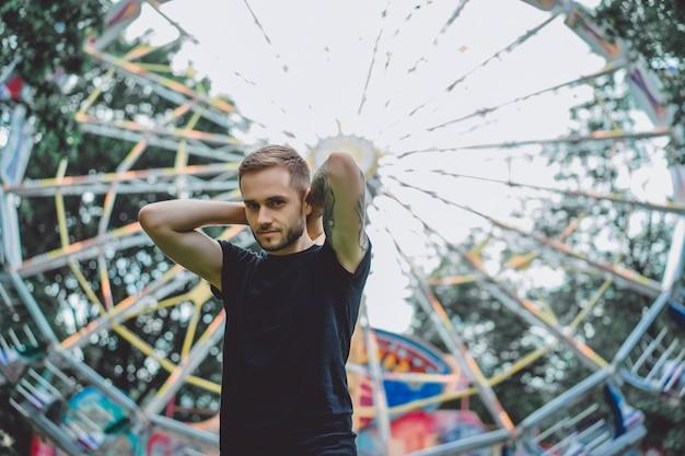 Jeune homme tatoué dans un parc d'attractions sur le fond d'un manège Photo gratuit