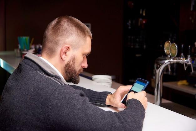 Jeune homme avec un téléphone dans un bar Photo Premium