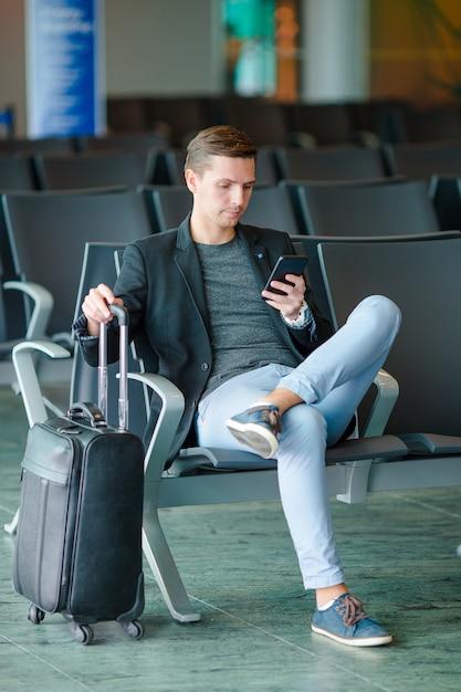 Jeune Homme Avec Un Téléphone Portable à L'aéroport En Attendant L'embarquement. Photo Premium