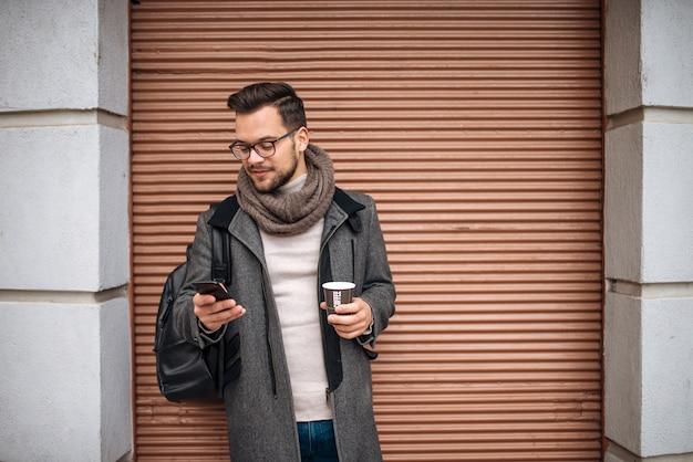 Jeune Homme Avec Un Téléphone Portable à La Main, Buvant Du Café à L'extérieur De La Ville. Photo Premium