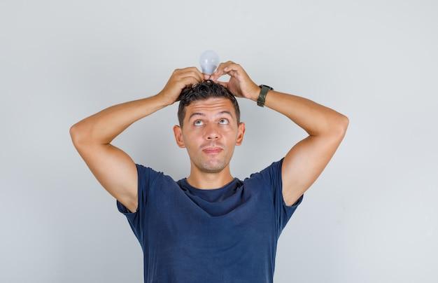 Jeune Homme Tenant Une Ampoule Sur Sa Tête En T-shirt Bleu Foncé Et à La Drôle, Vue De Face. Photo gratuit