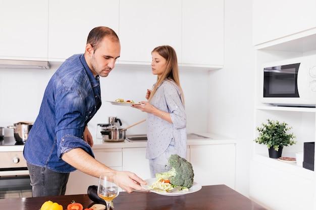 Jeune homme tenant l'assiette de salade dans la cuisine Photo gratuit