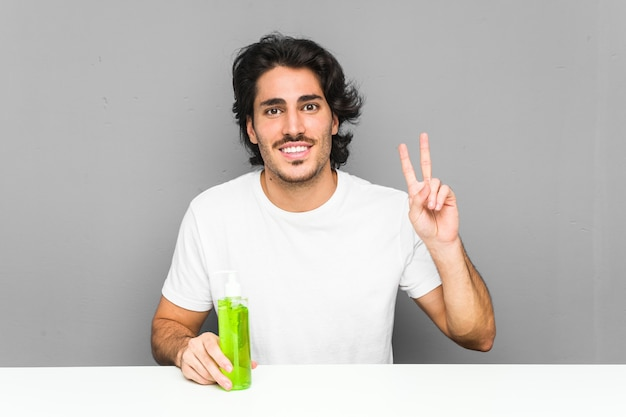 Jeune homme tenant une bouteille d'aloe vera montrant le signe de la victoire et souriant largement. Photo Premium