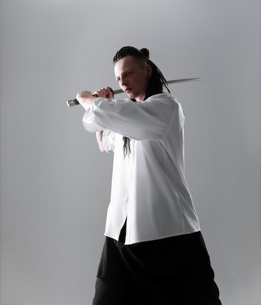 Jeune homme tenant une épée de samouraï. photo glamour. Photo Premium