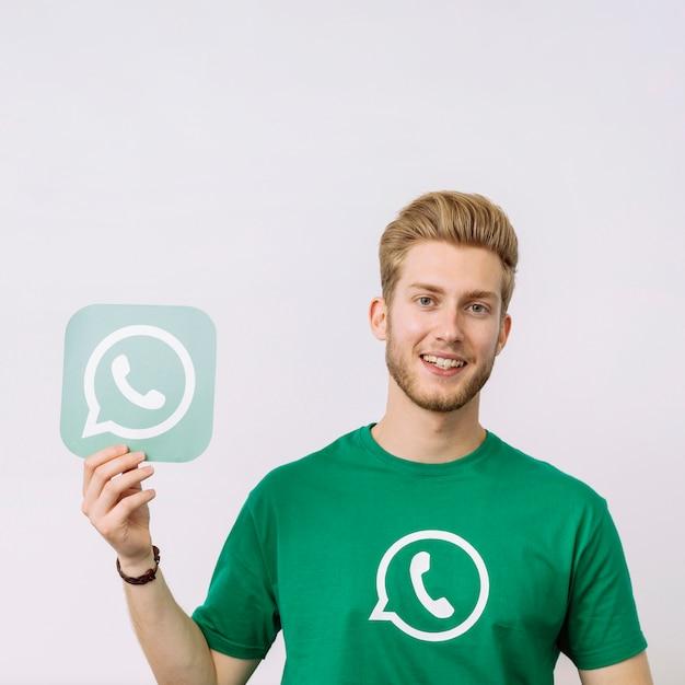 Jeune homme tenant l'icône whatsup sur fond blanc Photo gratuit