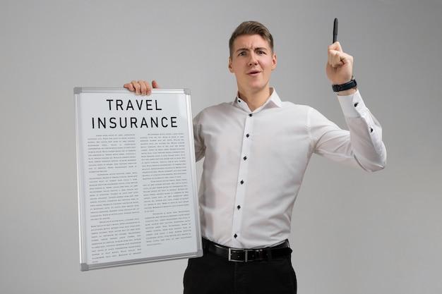 Jeune Homme Tenant Une Liste D'assurance Voyage Isolée Sur Fond Clair Photo Premium