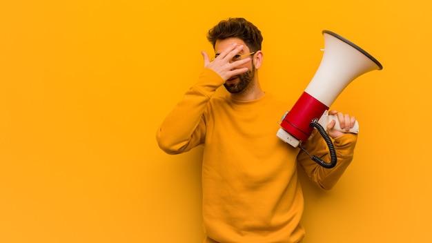 Jeune Homme Tenant Un Mégaphone Embarrassé Et Riant En Même Temps Photo Premium