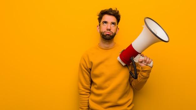 Jeune homme tenant un mégaphone fatigué et ennuyé Photo Premium