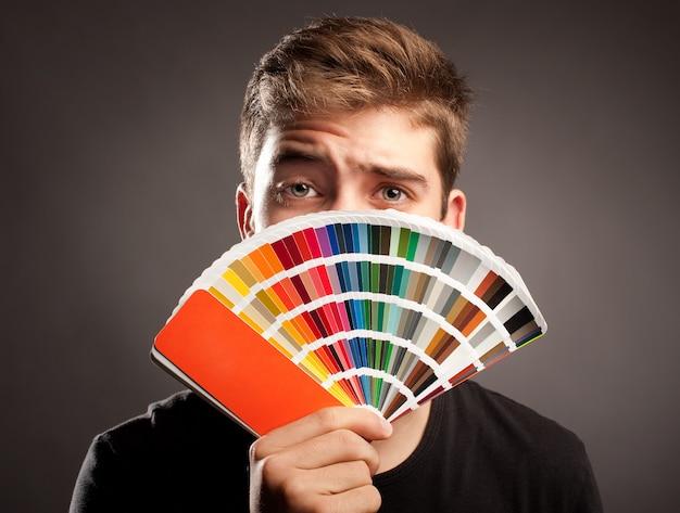 Jeune homme tenant une palette pantone Photo Premium