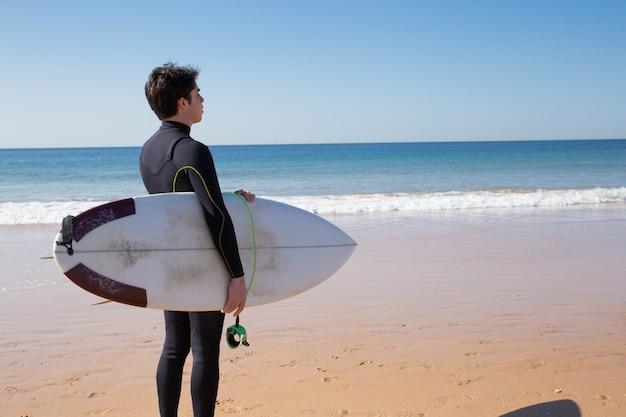 Jeune homme tenant une planche de surf et regardant la mer Photo gratuit