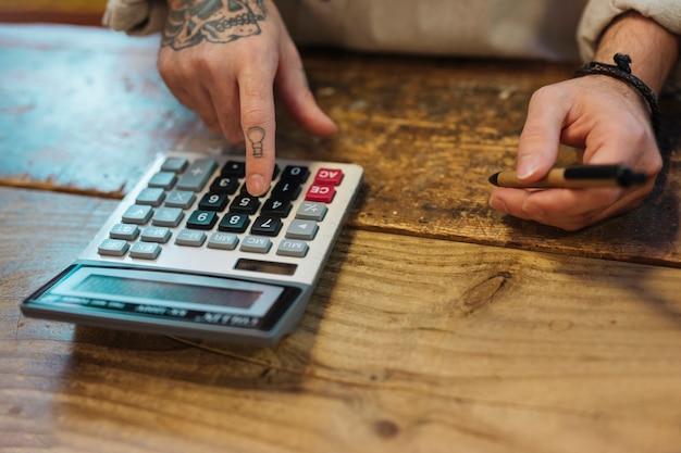 Jeune homme tenant un stylo à l'aide de la calculatrice dans son magasin Photo gratuit