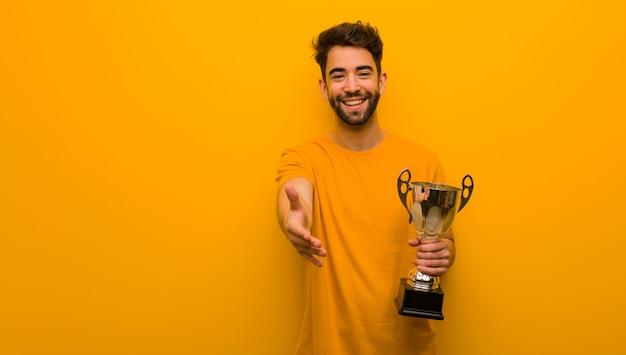 Jeune homme tenant un trophée tendre la main pour saluer quelqu'un Photo Premium