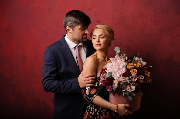 Jeune Homme Tenir Sa Femme Sur L'épaule Avec Le Bouquet De Fleurs Photo Premium