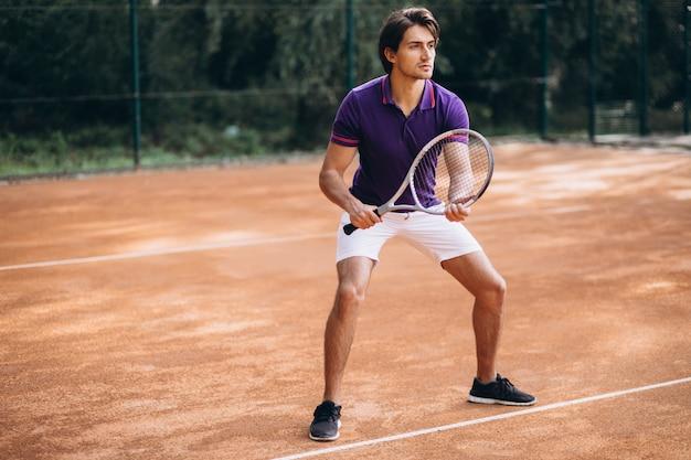 Jeune homme tennisman sur le court Photo gratuit