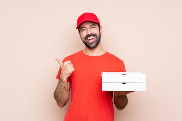Jeune homme, tenue, pizza, pouces, geste, sourire Photo Premium