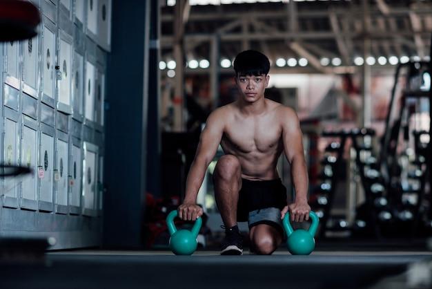 Jeune homme en tenue de sport une classe d'exercices dans une salle de sport Photo gratuit