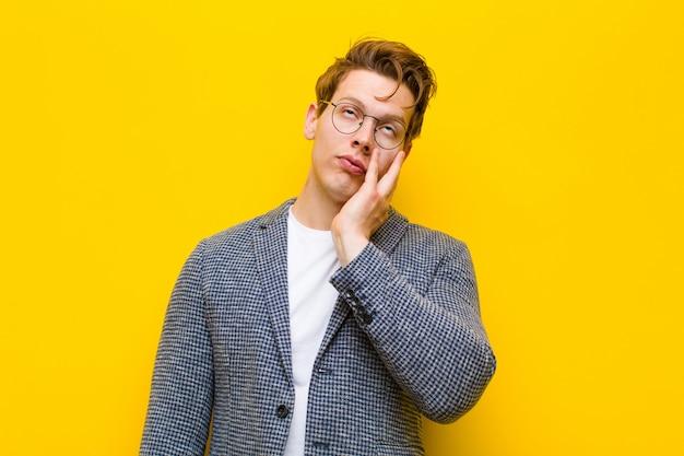 Jeune homme à la tête rouge se sentant ennuyé, frustré et somnolent après une tâche fastidieuse, ennuyeuse et fastidieuse, tenant son visage avec la main Photo Premium