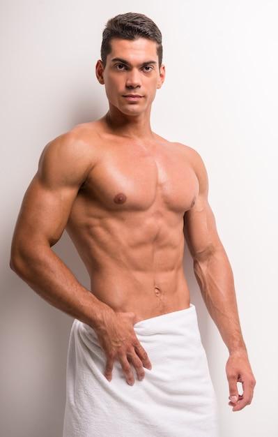 Jeune homme torse nu recouvert d'une serviette. Photo Premium