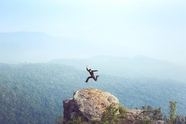 Jeune homme touriste asiatique à la montagne veille sur le lever du soleil brumeux et brumeux Photo Premium