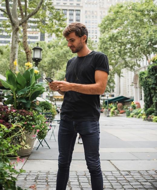 Jeune homme en train de taper au téléphone Photo gratuit