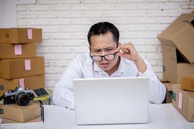 Jeune homme travaillant au marketing en ligne avec ordinateur portable et boîte aux lettres Photo gratuit