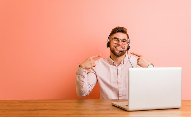 Jeune homme travaillant dans un centre d'appels sourit et pointe ses doigts vers la bouche. Photo Premium