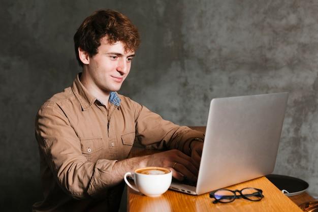 Jeune homme travaillant sur l'ordinateur portable au bureau Photo gratuit