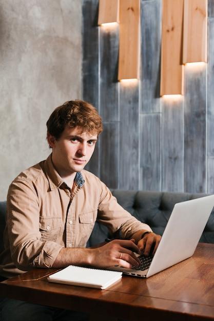 Jeune homme travaillant sur l'ordinateur portable Photo gratuit