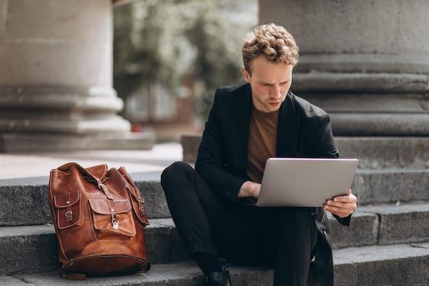 Jeune homme travaillant sur un ordinateur à l'université Photo gratuit