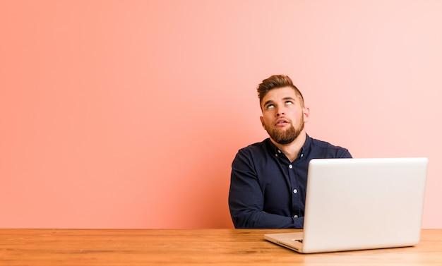 Jeune homme travaillant avec son ordinateur portable fatigué d'une tâche répétitive Photo Premium