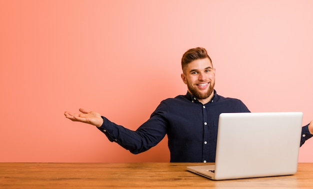 Jeune homme travaillant avec son ordinateur portable montrant une expression bienvenue. Photo Premium