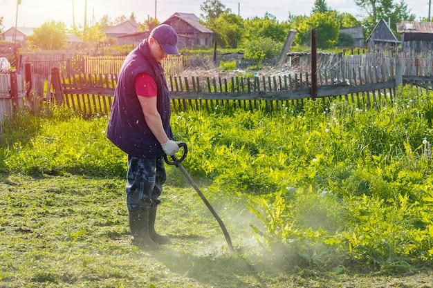 Jeune Homme Travaille Avec Coupe-bordures Couper L'herbe Dans Le Jardin Photo Premium