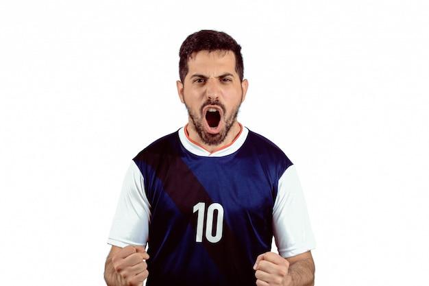 Jeune homme en uniforme de football soccer hurlant pendant que son équipe gagne. Photo Premium