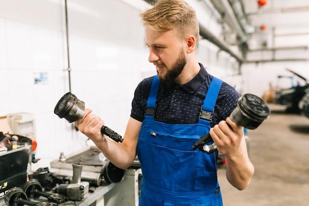 Jeune homme en uniforme tenant des pistons de moteur Photo gratuit