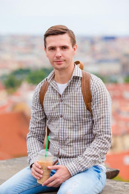 Jeune homme urbain, boire, café, fond, ville européenne, dehors Photo Premium