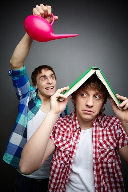 Jeune homme utilisant un livre comme un parapluie Photo gratuit