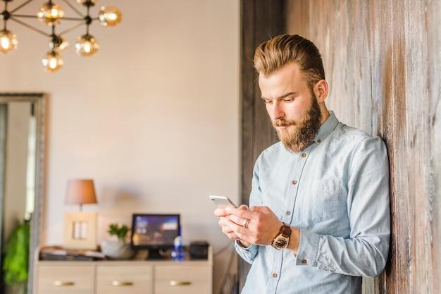 Jeune homme utilisant un smartphone à la maison Photo gratuit