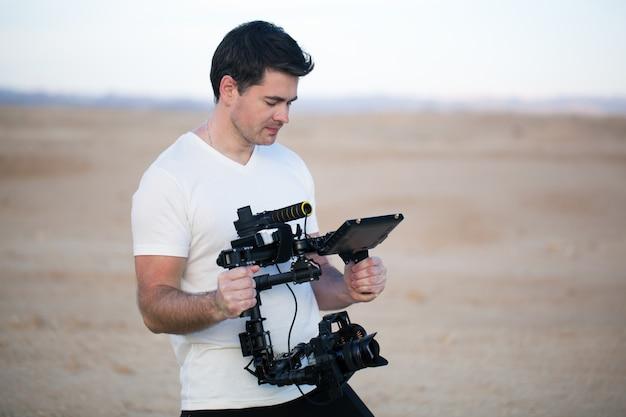 Jeune homme utilisant steadycam pour le tir sur la plage Photo Premium