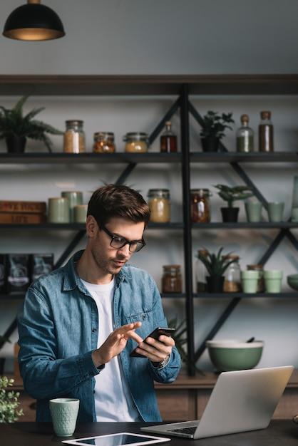 Jeune homme utilisant un téléphone portable avec un ordinateur portable; tablette numérique et une tasse de café sur le comptoir de la cuisine Photo gratuit