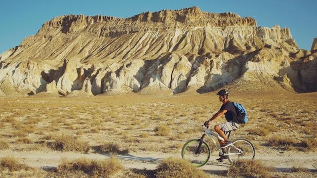 Jeune homme à vélo sur un fond de paysage avec des montagnes Photo Premium