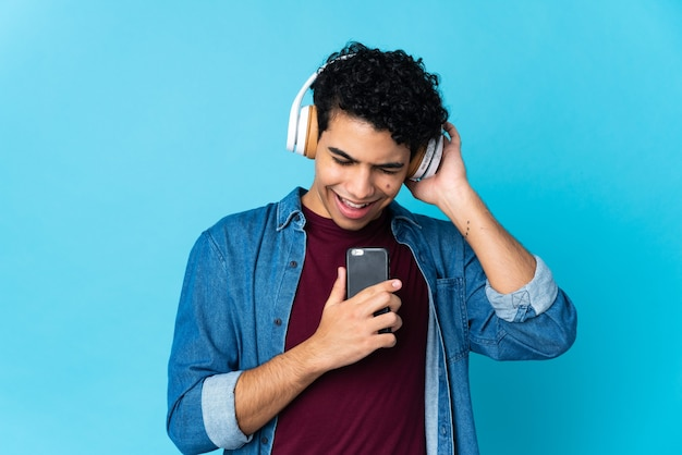 Jeune Homme Vénézuélien Isolé Sur Bleu écoute De La Musique Avec Un Mobile Et Le Chant Photo Premium