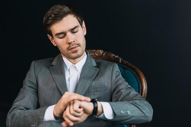 Jeune homme vérifiant l'heure sur sa montre sur fond noir Photo gratuit