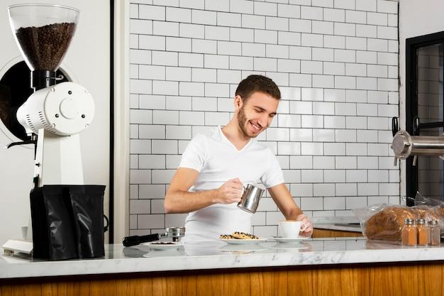 Jeune Homme Versant Du Lait Dans Une Tasse De Café Photo gratuit