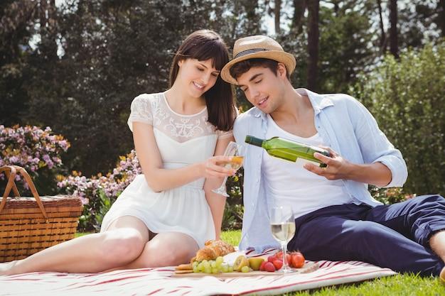 Jeune homme verse à la femme du vin dans un verre lors d'un pique-nique Photo Premium