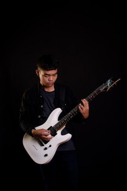 Jeune homme en veste de cuir noir avec guitare électrique Photo gratuit
