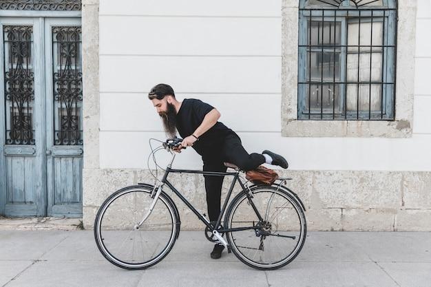 Jeune homme en vêtements noirs assis sur un vélo au-dessus de la rue Photo gratuit