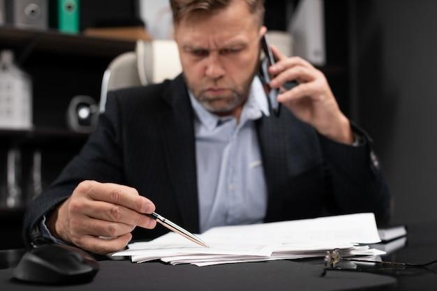 Jeune homme en vêtements de travail travaillant à l'ordinateur de bureau avec téléphone et documents Photo Premium