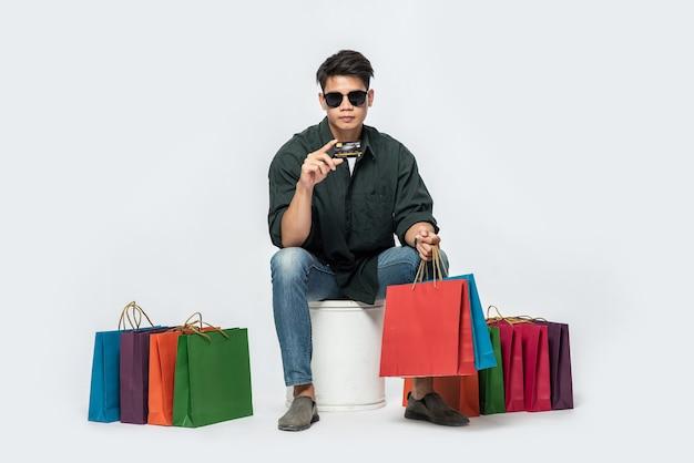 Un Jeune Homme Vêtu D'une Chemise Sombre Et D'un Jean, Portait Plusieurs Sacs Pour Faire Du Shopping Avec Une Carte De Crédit Photo gratuit